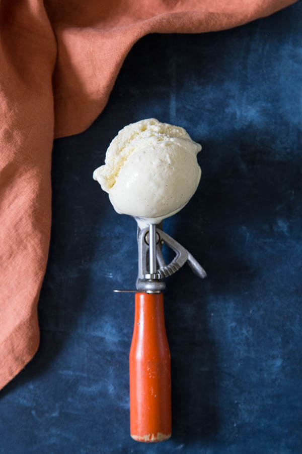 A scoop of lactose free vanilla ice cream in an ice cream scoop