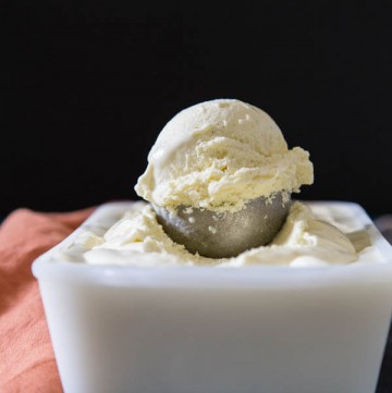 A scoop of lactose free ice cream on top of the ice cream container
