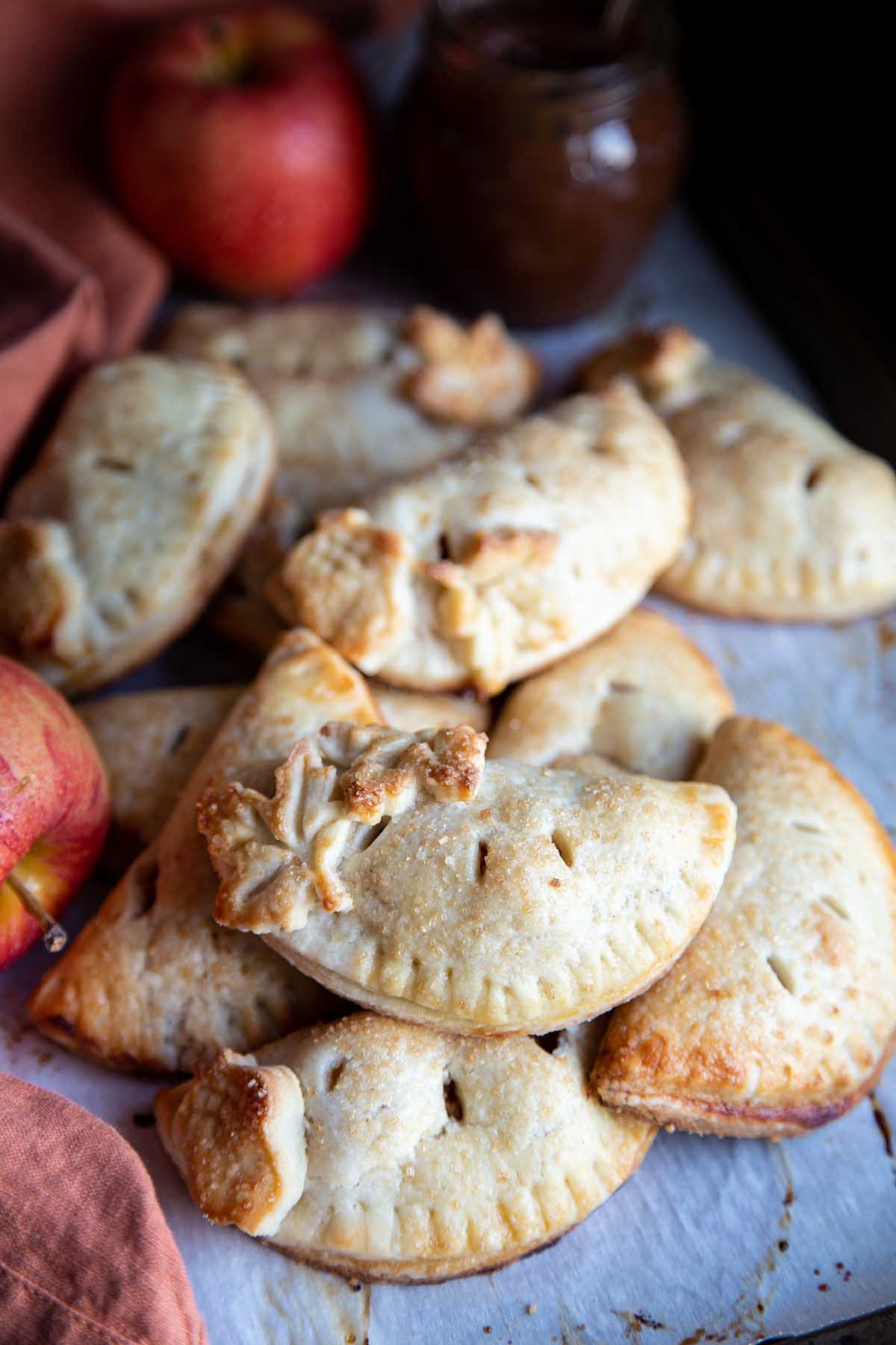 Apple hand pies piled on a baking sheet