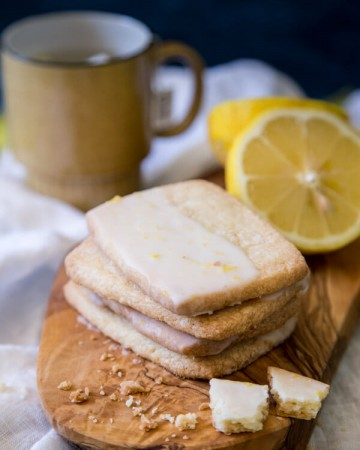 Lemon Shortbread Cookies on a wooden board with lemon halves