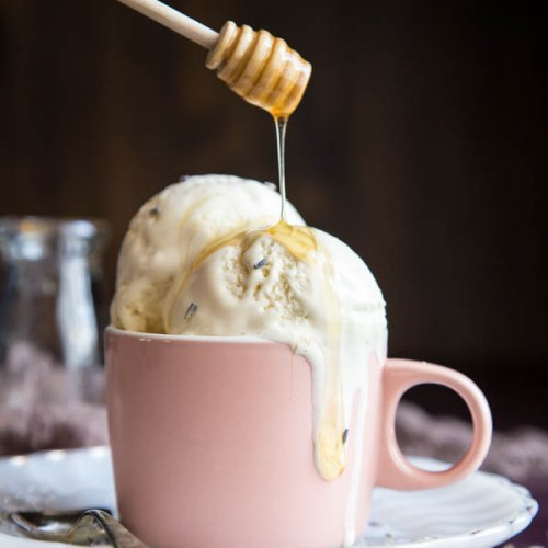 Honey drizzling into a cup of lavender ice cream