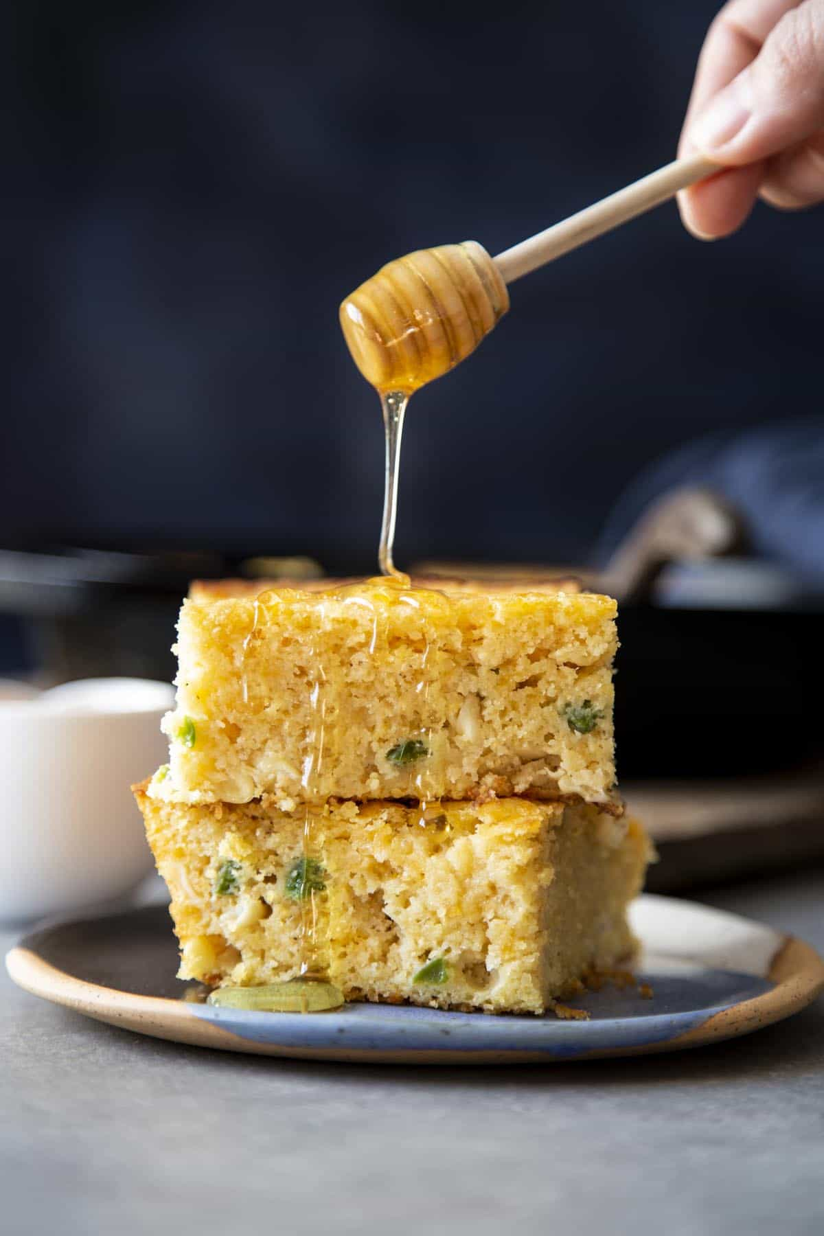 A stack of 2 cornbread being drizzled with honey.