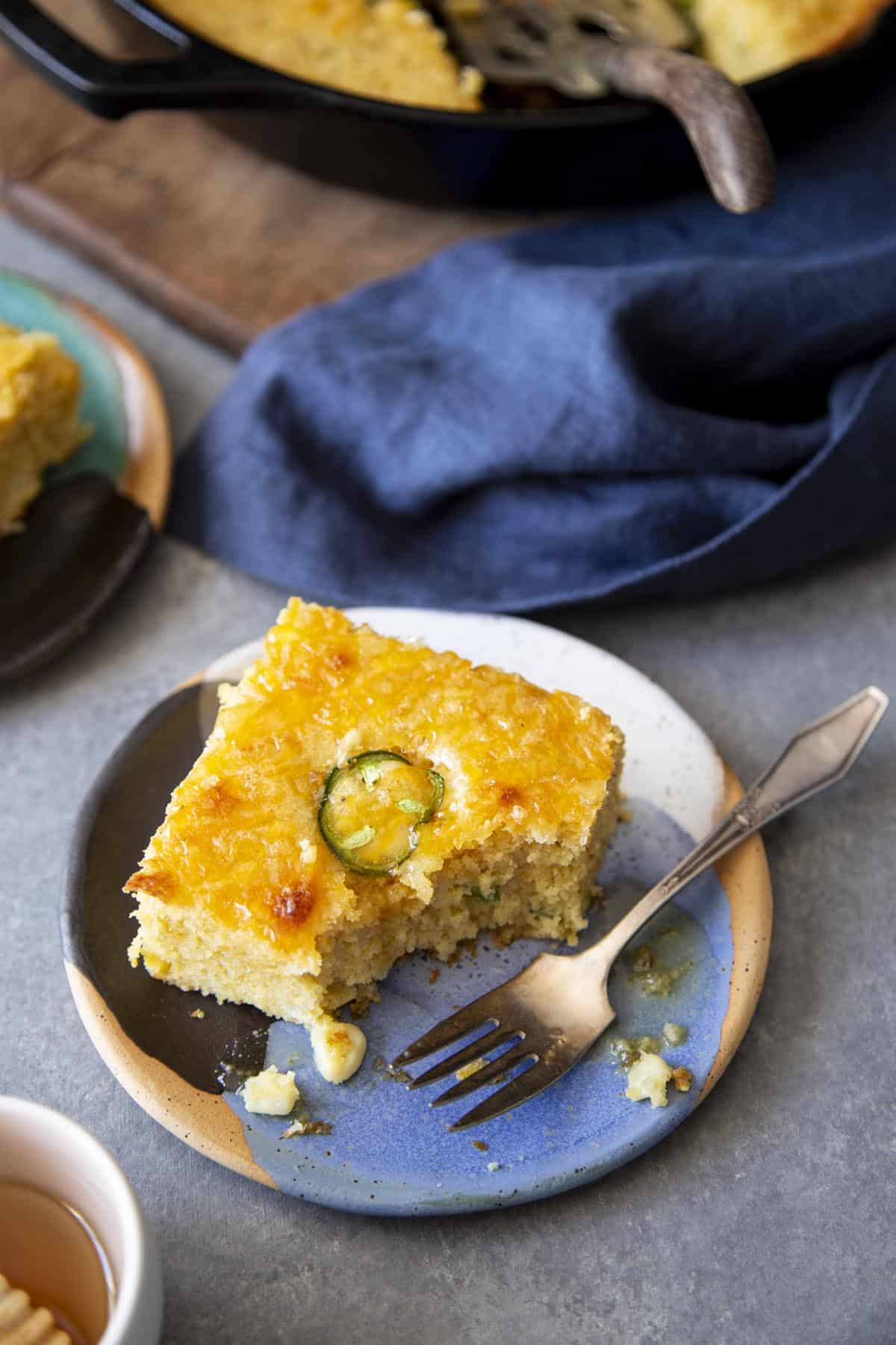 A slice of Jalapeno Cheddar Cornbread on a plate with a fork.