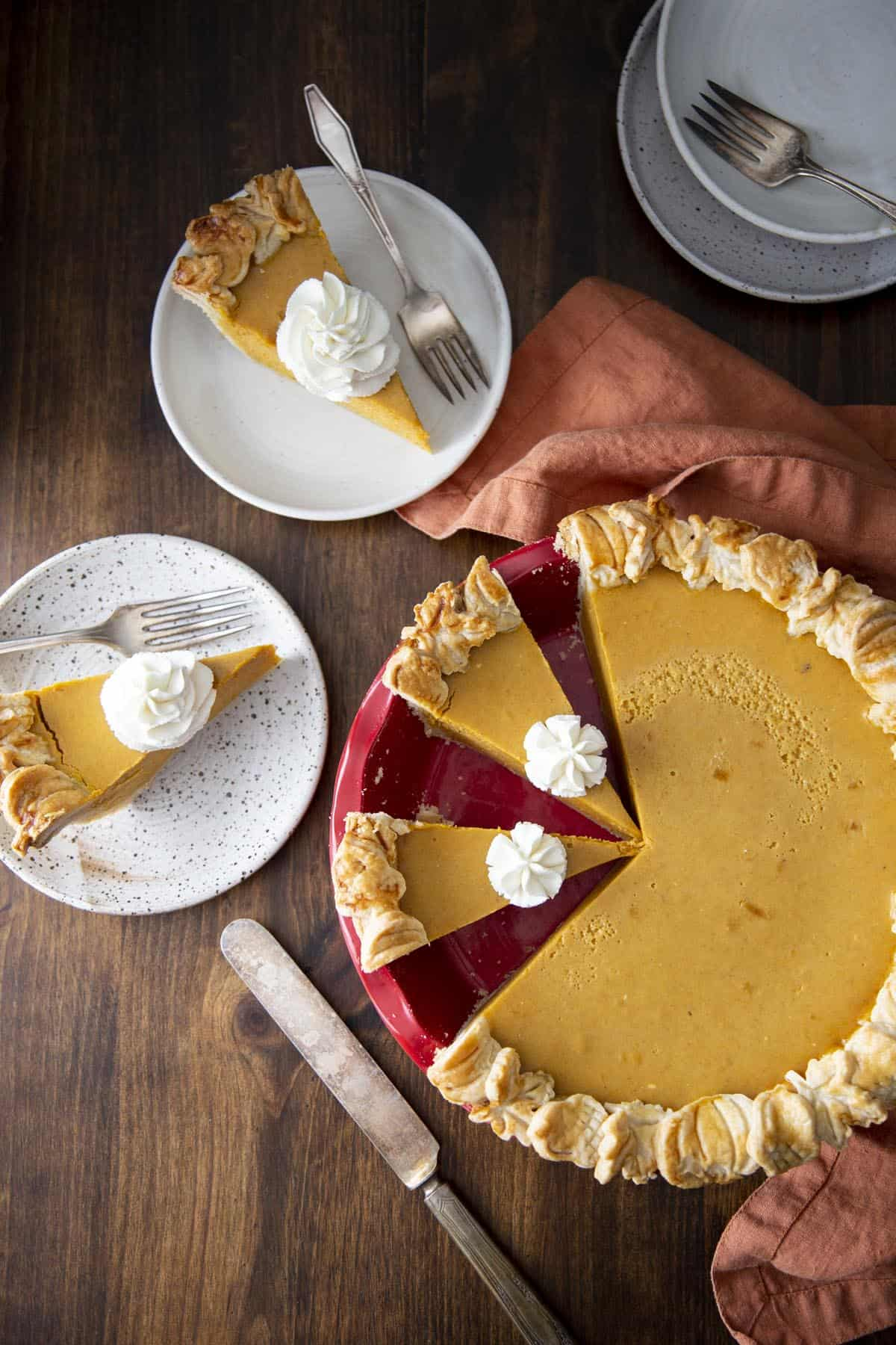A pumpkin pie in a red pie dish and slices of pumpkin pies on plates