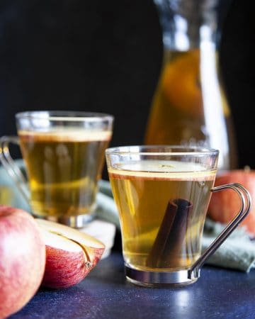 2 glasses of apple ciders next to some apple and a serving jug