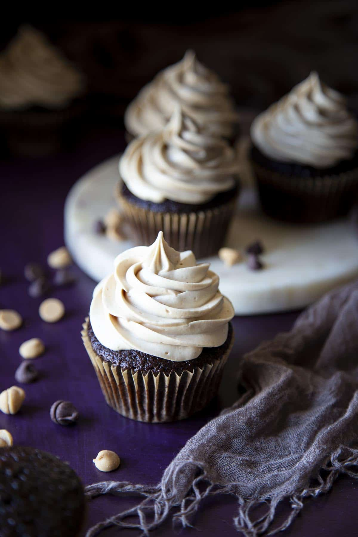 Several chocolate cupcakes with peanut butter frosting on a purple surface with a gray towel