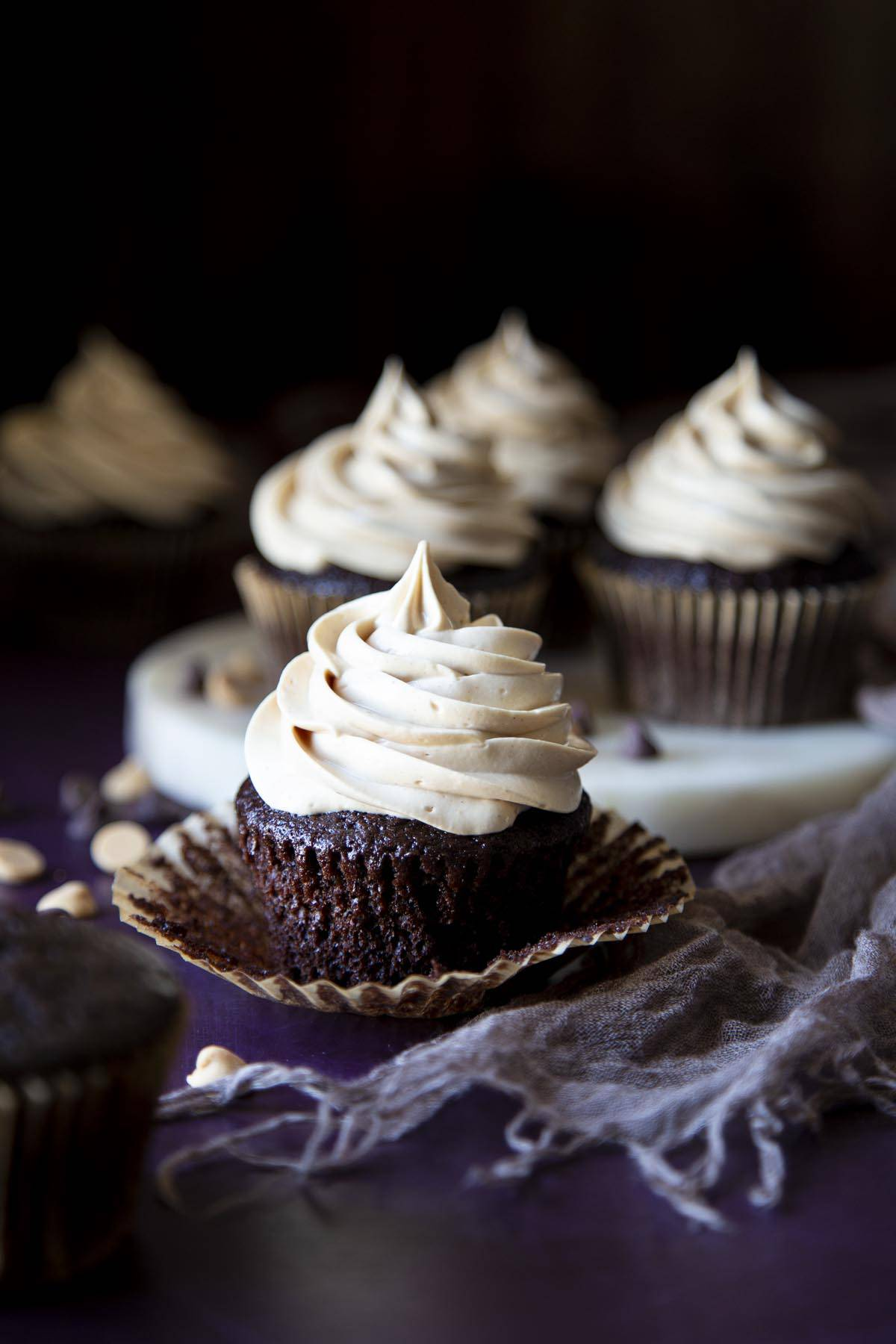 A chocolate peanut butter cupcake with the cupcake paper peeled off, more cupcakes in the background