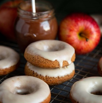 Glazed baked donuts on a wire rack with a jar of apple butter