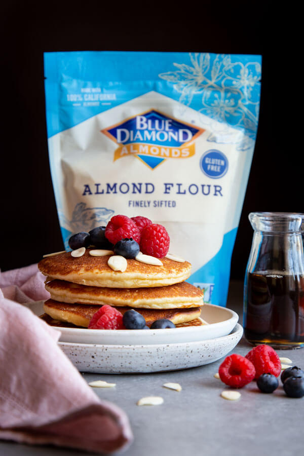 A stack of almond pancakes on a plate next to a bag of almond flour
