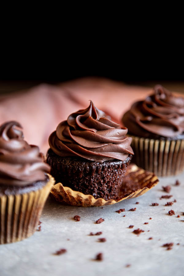 Three chocolate cupcakes standing in a line