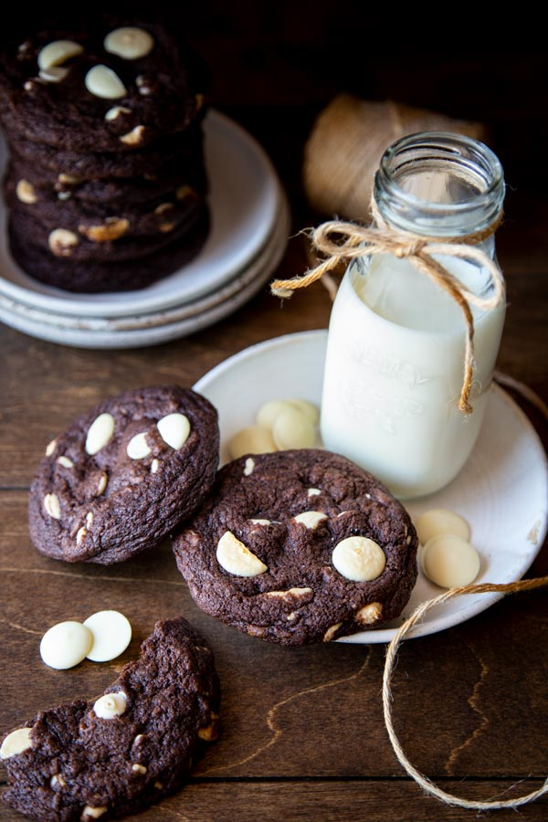 Chocolate white chocolate chip cookies on a plate with a bottle of milk
