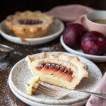 A mini plum tart cut in half on a plate
