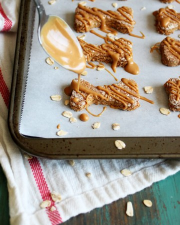 Drizzling peanut butter over apple dog treats on a baking tray