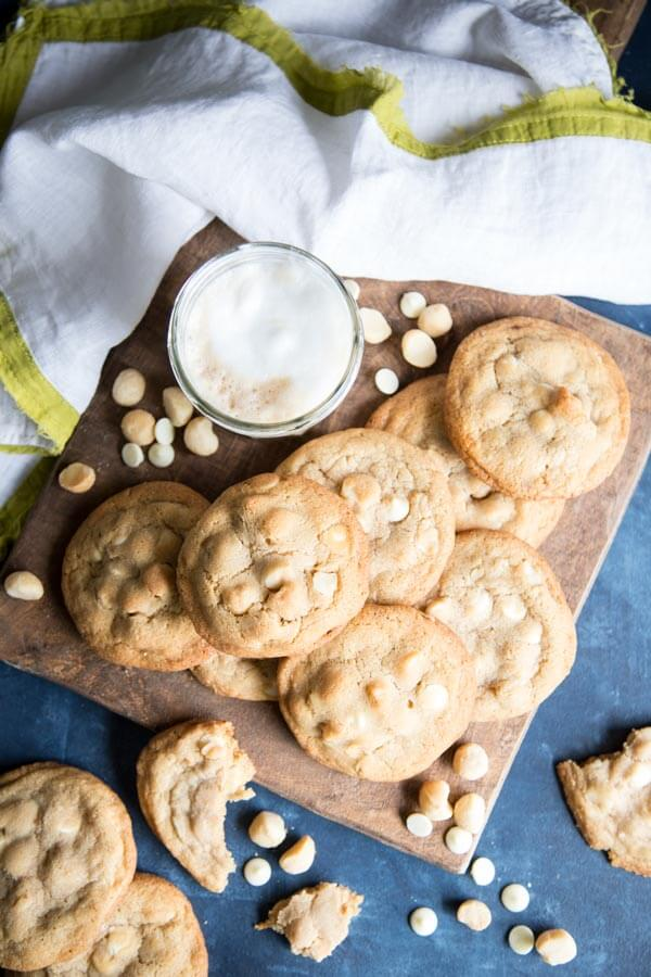 A pile of white chocolate macadamia nut cookies on a wooden board