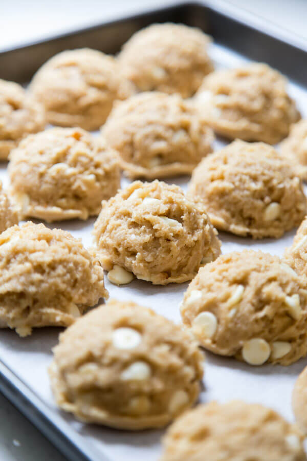 White chocolate macadamia nut cookie dough balls on a baking sheet