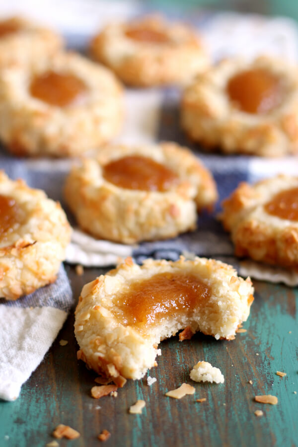 These Coconut Guava Thumbprint Cookies are like buttery little tropical gems covered in coconut flakes and topped with a dollop of guava jam!   wildwildwhisk.com