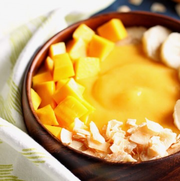 Mango peach smoothie in a wooden bowl