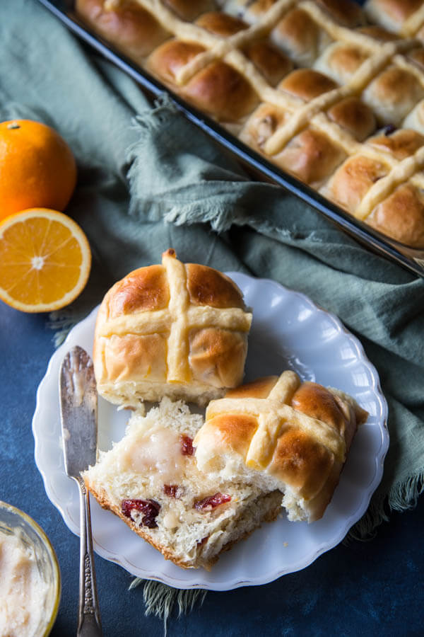 Orange cranberry hot cross buns with butter on a plate