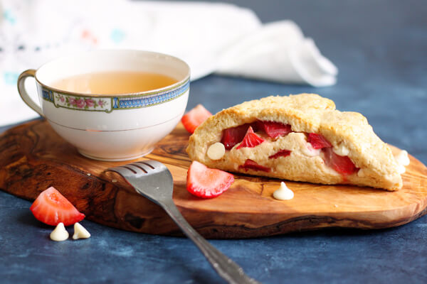 A strawberry scone next to a tea cup