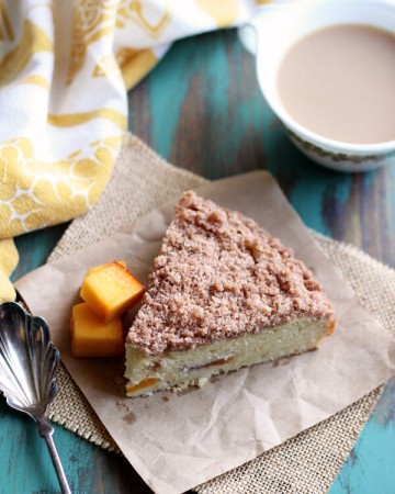 A slice of peach coffee cake on brown paper square
