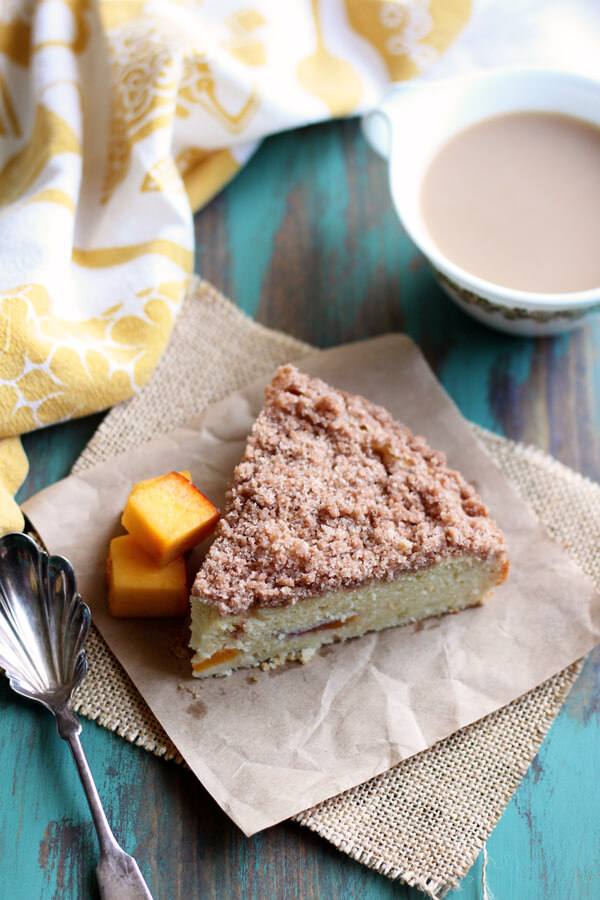 This Peach Coffee Cake has a wonderful crumbly cinnamon streusel topping. The addition of cream cheese in the batter yields an exceptionally moist cake! | wildwildwhisk.com