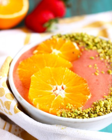 Strawberry orange smoothie in a bowl garnished with orange slices and pistachio