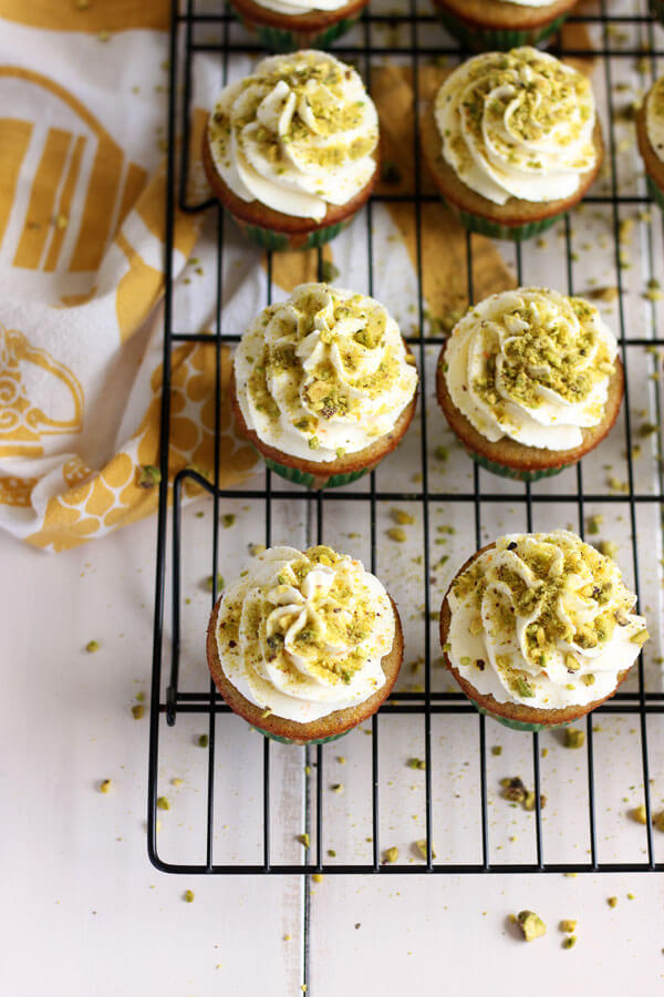 Pistachio Cupcakes with Orange Mascarpone Frosting garnished with ground pistachio | wildwildwhisk.com