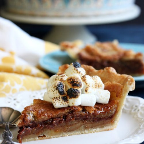This S'mores Bomb Pie tastes like campfire s'mores on steroid. It is an intensely decadent dessert that will blow your mind!   wildwildwhisk.com