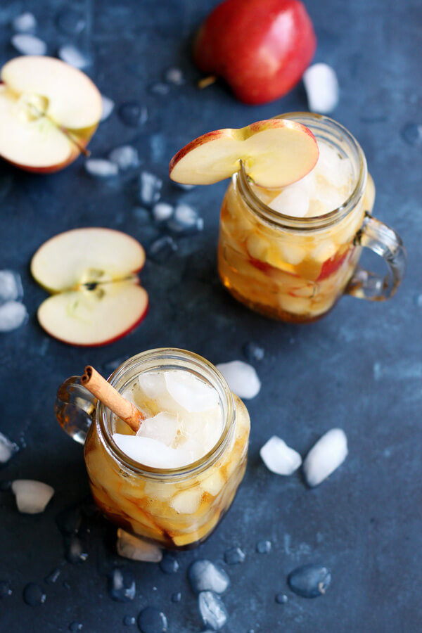 A photo of two Autumn Pimm's Cup on a blue board scattered with ice cubes and sliced apples.
