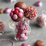 Strawberry truffles on a stick in a small jar