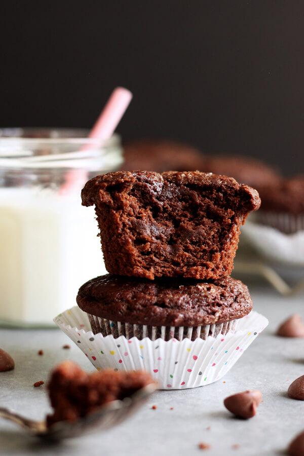A stack of two Chocolate Coconut Yogurt Muffins, a bite was taken out of the top one