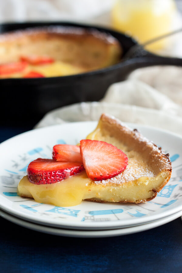 A slice of Lemon Dutch Baby with lemon curd dripping on the side