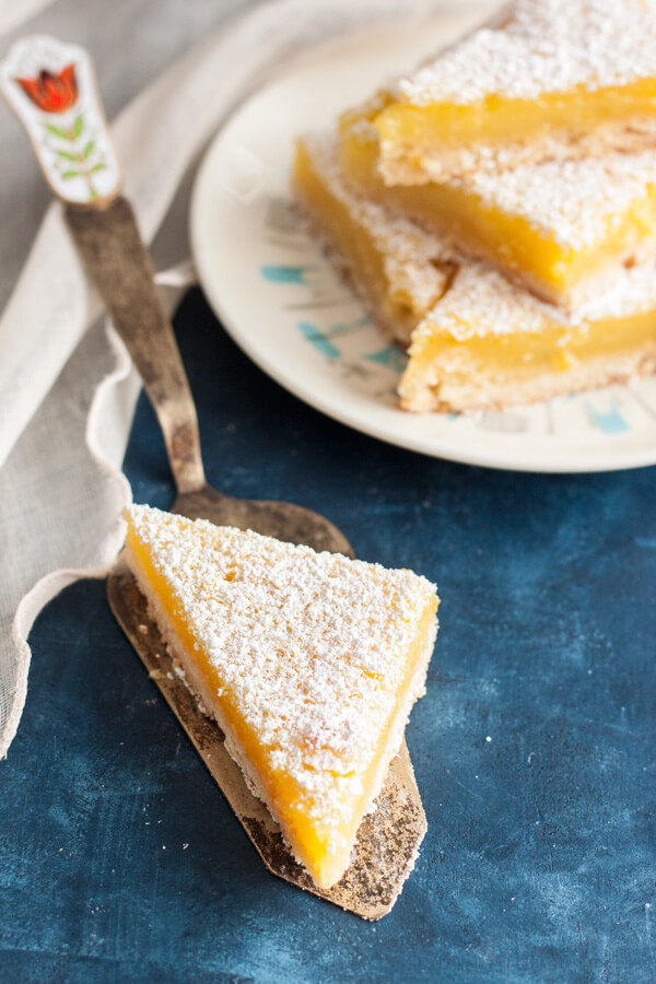 Lemon Bars with Shortbread Crust on a plate and a vintage spatula