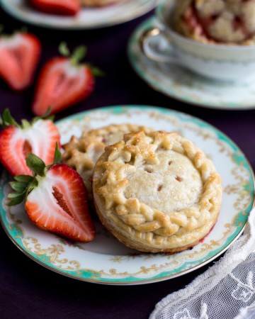 Strawberry Compote Hand Pies on a plate next to fresh strawberries