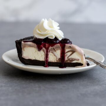 A slice of No Bake Ice Cream Pie with Cherry Compote and Whipped Cream
