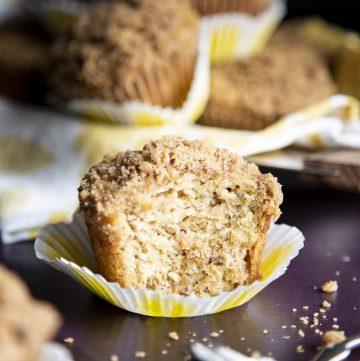A half eaten banana nut muffin sitting on cupcake liner.