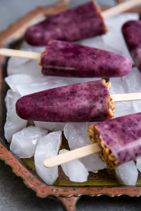 Blueberry Popsicles laying on top of ice cubes on a tray