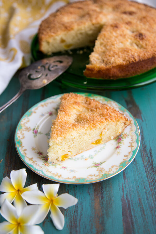 A slice of Tropical Peach Mango Coconut Cake with Mascarpone on a plate