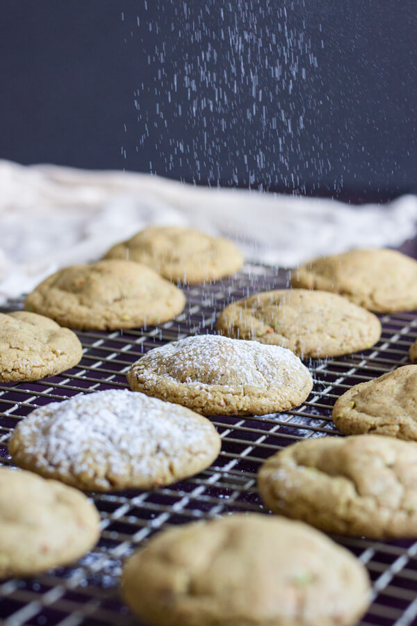 Pistachio Butter Cookies being dusted with powder sugar