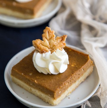 Pumpkin Pie Shortbread Bars garnished with whipped cream and a pie crust maple leaf
