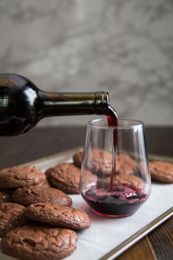 Dark Chocolate Brownie Cookies on a baking sheet with wine being poured into a glass