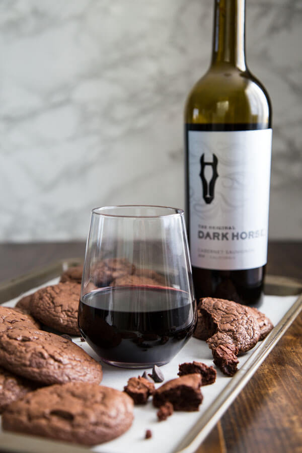 Dark Chocolate Brownie Cookies and wine on a baking sheet