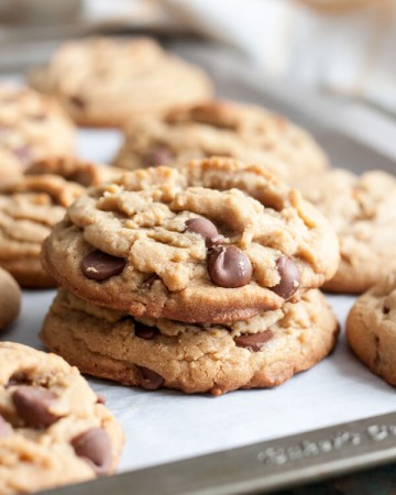 A stack of two peanut butter chocolate chip cookies on a baking sheet