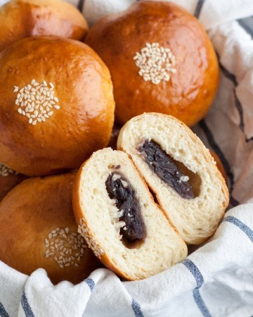 Anpan or Japanese Red Bean Buns in a basket with one cut open