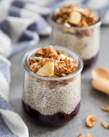 Coconut Chia Pudding with berry compote and granola in glass jars