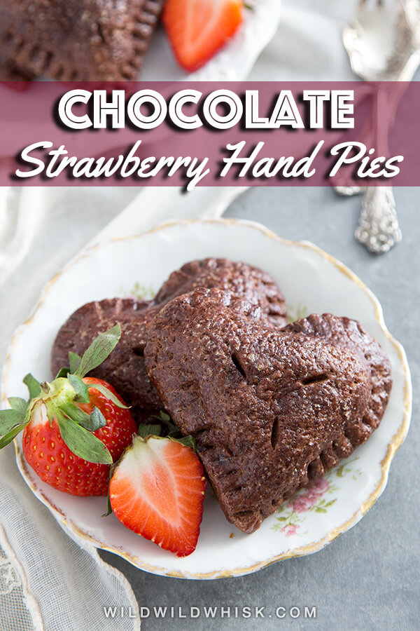 These heart shape Strawberry Hand Pies are made with a homemade chocolate pie crust. This recipe perfect for Valentine's Day. #wildwildwhisk #handpies #strawberrypie #strawberryrecipes #valentines #valentinesday #valentinesdaytreats #valentinesdaydesserts #valentinesdayideas