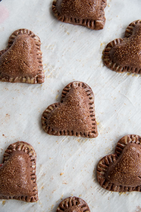 Unbaked Chocolate Strawberry Hand Pies on a baking sheet
