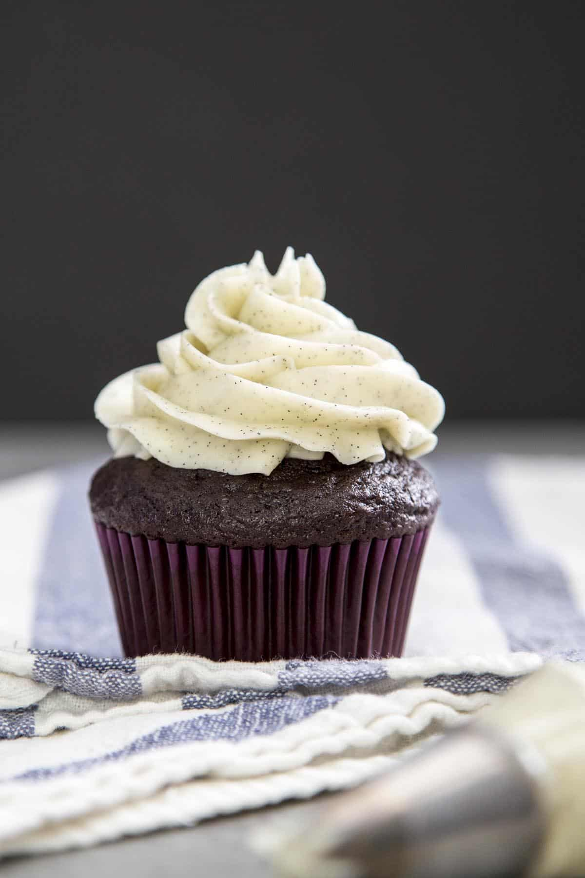 Vanilla bean swiss buttercream frosting on top of a chocolate cupcake