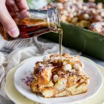 Maple syrup is being pour over a piece of almond croissant french toast bake