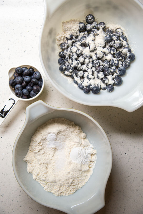 A mixing bowl with blueberries and flour next to another mixing bowl with a flour mixture next to a measuring cup with some fresh blueberries